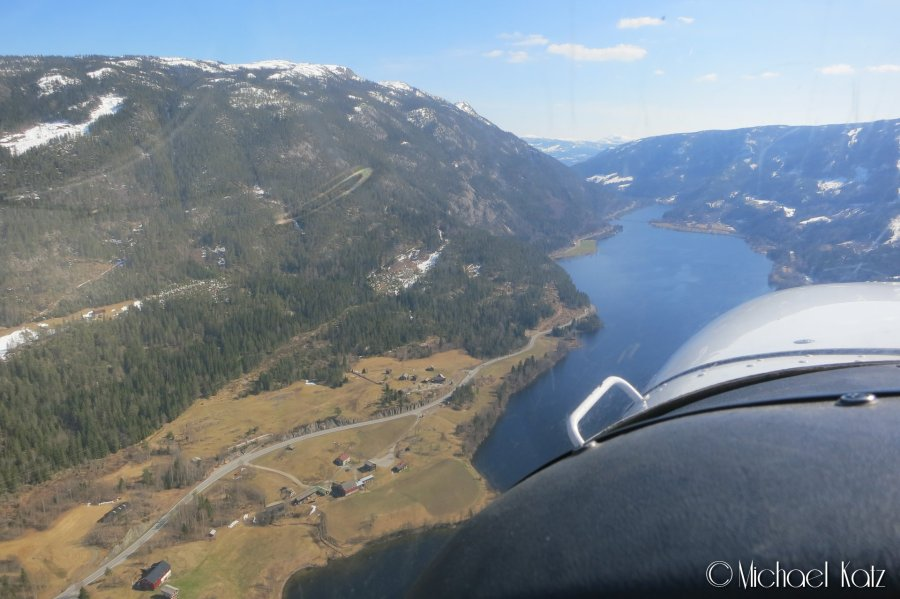 Cessna suser forbi bilene under, som snirkler seg frem i Numedal .