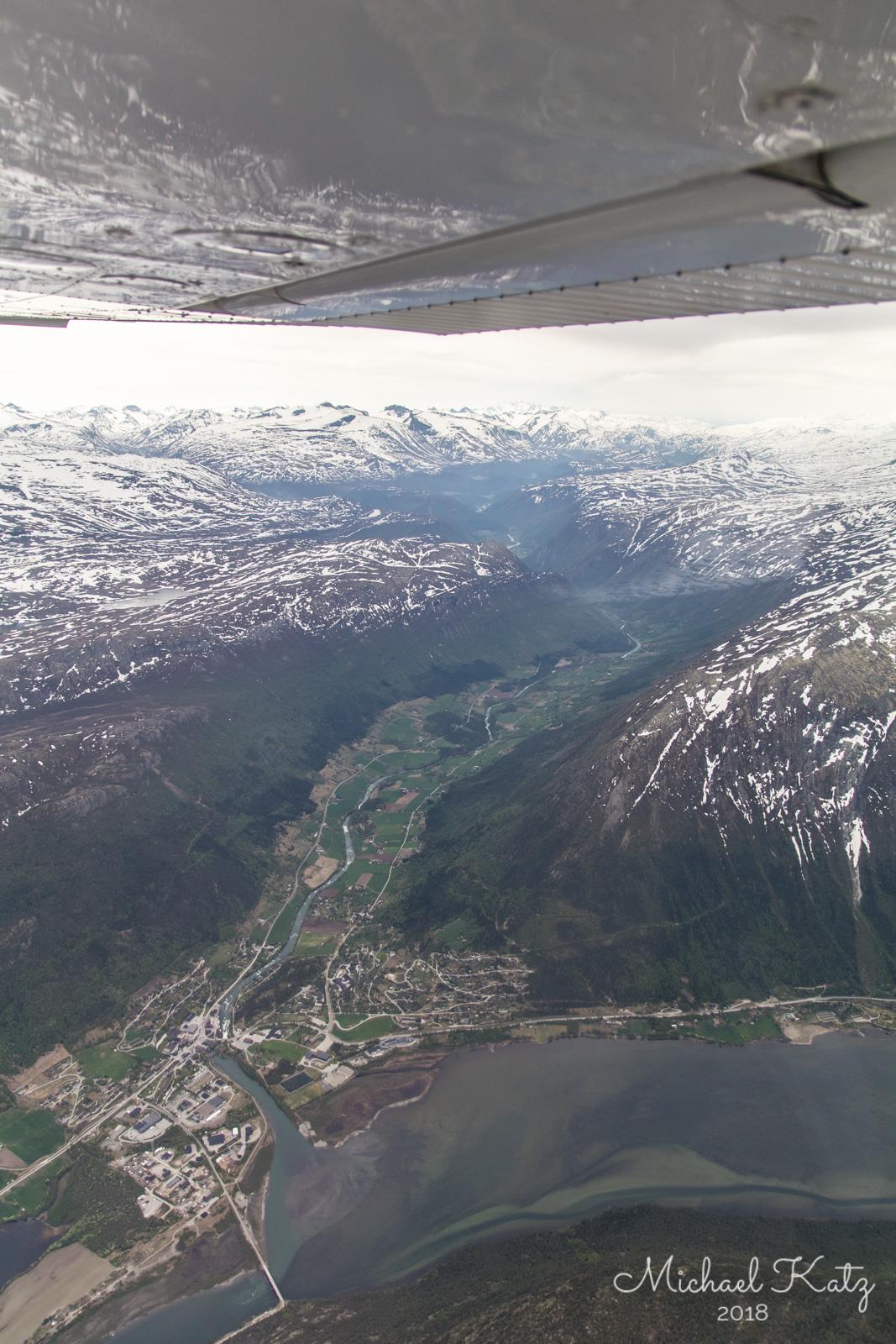 Vi snur tilbake pga. for sterk vind over fjellene! Her flyr vi over Lom og ser innover Ottadalen langs riksvei 15 mot Geiranger.
