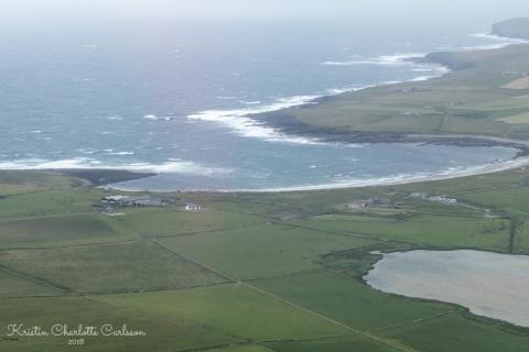 Utsikt over Bay of Skaill med Skara Brae i forgrunnen.